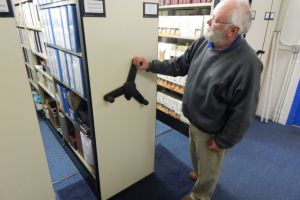 A volunteer shows how easy it is to move the shelves in the back room